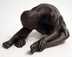 frontal sinister lateral view of a bronze sculpture of a male nude sitting with his head on his knee