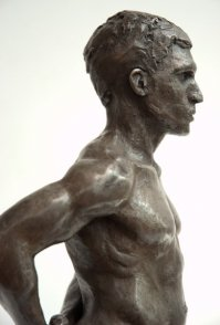 lateral view of bust of bronze sculpture of male nude standing figure