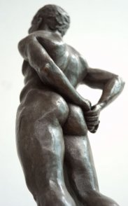 caudal lateral dorsal view of bronze sculpture of male nude standing figure