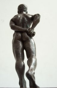 caudal dorsal view of bronze sculpture of standing male nude figure