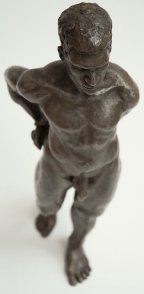 cranial frontal view of bronze sculpture of male nude standing figure