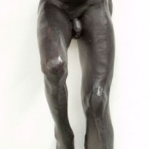 bronze sculpture of a male nude sitting and leaning back on his arms